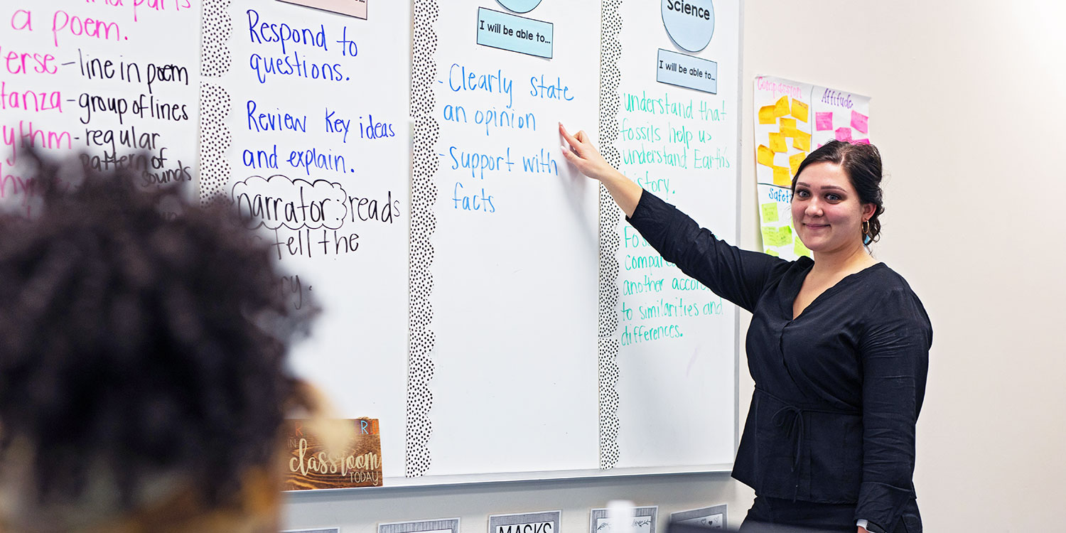 Teacher smiling and pointing to a lesson on a white board in a classroom.